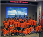 Large group of students in orange pose together for picture